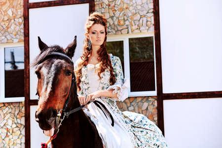 middeleeuwse jurk: Mooie jonge vrouw in middeleeuwse kleding paardrijden outdoor.