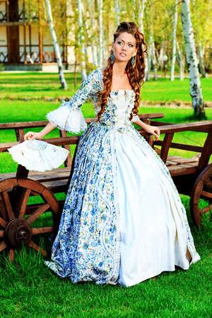 vestido medieval: Hermosa mujer joven en la época medieval vestido en un día soleado al aire libre. Foto de archivo