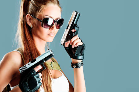Shot of a sexy military woman posing with guns. Stock Photo - 10075875