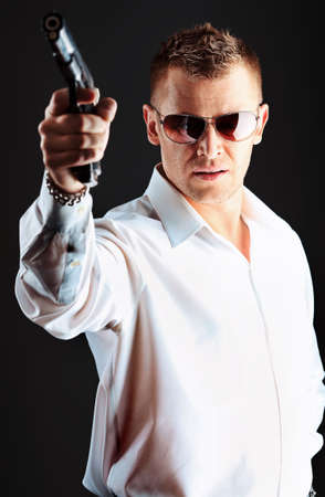 bodyguard: Portrait of a handsome man holding a gun. Studio shot. Stock Photo