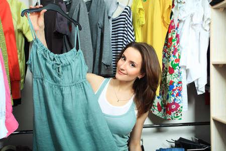 Hermosa mujer mirando su ropa en un armario en su casa.