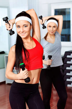 gym class: Two young sporty woman in the gym centre.