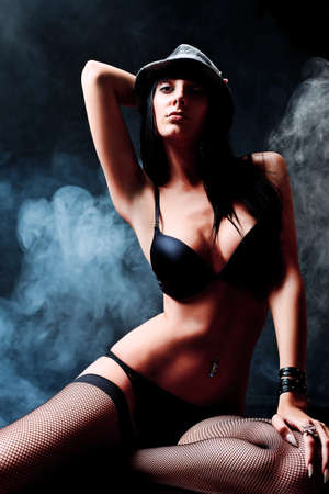 hat nude: Shot of a sexy woman in black lingerie over dark background with smoke.