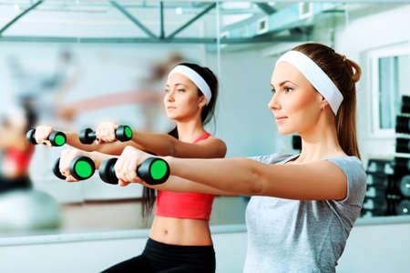 ejercicio aer�bico: Dos mujeres j�venes deportivo en el centro de gimnasio.