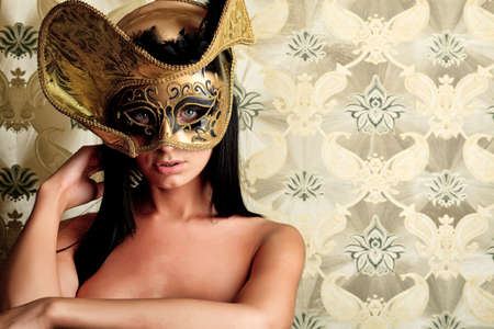 Shot of a sexy woman in a mask over vintage background. Stock Photo - 10213516