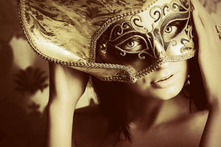 nude brunette: Shot of a sexy woman in a mask over vintage background.