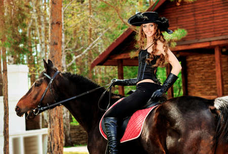 musketeer: Beautiful young woman in medieval costume is riding on horseback. Stock Photo