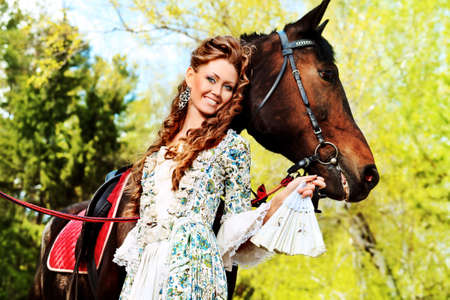historical clothing: Beautiful young woman in medieval dress with a horse outdoor.
