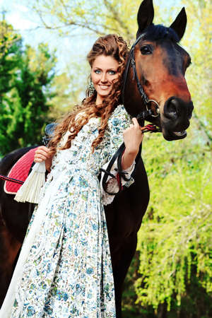 riches adult: Beautiful young woman in medieval dress with a horse outdoor.