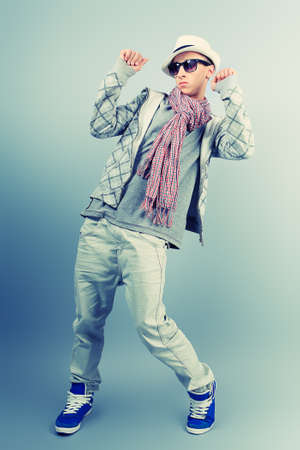 dance pose: Young man dancing hip-hop at studio. Stock Photo