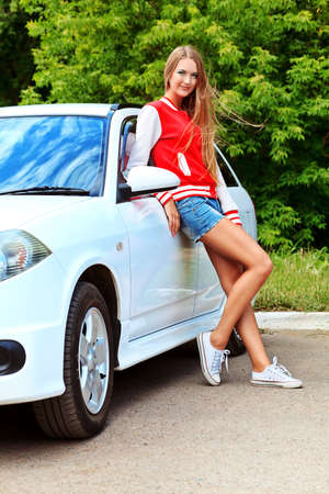 Happy young woman having summer trip on a car. photo
