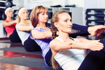 abdominal fitness: Grupo de mujeres jóvenes en el centro de gimnasio.
