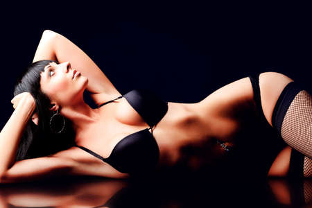 Shot of a sexy woman in black lingerie over black background. Stock Photo