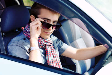 Handsome young man having summer trip on a car. photo