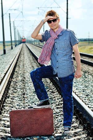 Retrato de un joven apuesto posando en un ferrocarril.
