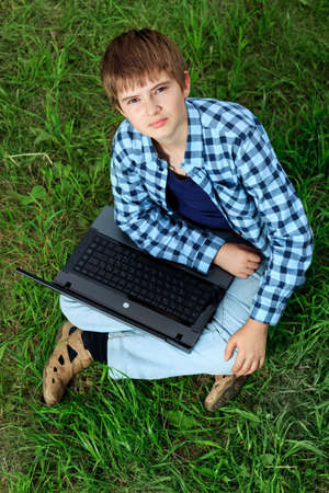 Portrait of a boy teenager sitting with his laptop on a grass at a park. Stock Photo - 10348848