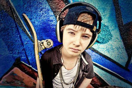 boy skater: Portrait of a trendy boy teenager with skateboard outdoors.