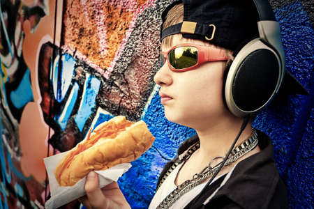 Portrait of a modern boy teenager eating hot dog outdoors. photo