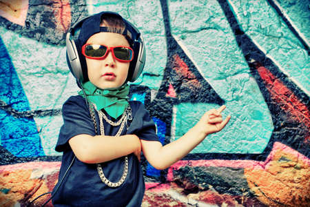 Portrait of a trendy little boy  with headphones outdoors.