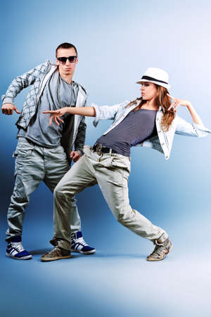 dancing pose: A couple of young man and woman dancing hip-hop at studio. Stock Photo