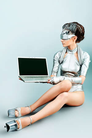 concept magical universe: Shot of a futuristic young woman with a laptop.  Stock Photo