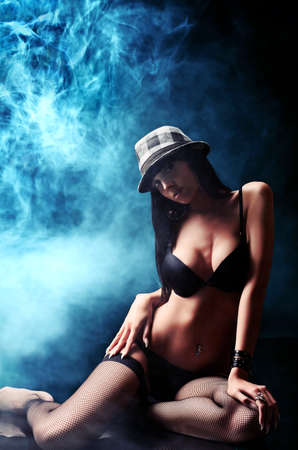 Shot of a sexy woman in black lingerie over dark background with smoke. Stock Photo - 10385345