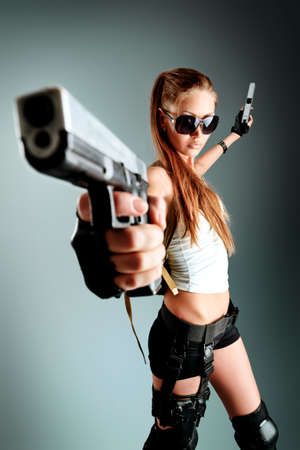 Shot of a sexy military woman posing with guns. Stock Photo - 10418906