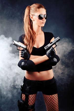 Plan d'une femme sexy posant avec des armes militaires.
