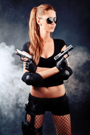 Shot of a sexy military woman posing with guns. photo