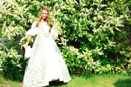 aristocrat: Beautiful young woman in medieval era dress on a sunny day outdoor. Stock Photo