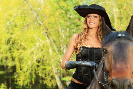 horseback: Beautiful young woman in medieval costume is riding on horseback. Stock Photo