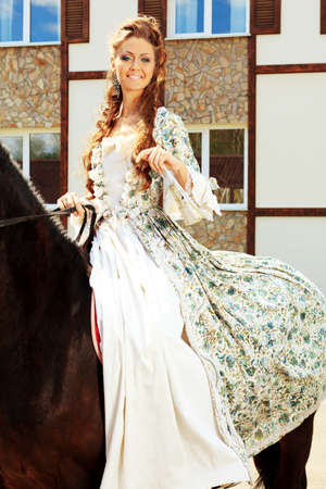 middeleeuwse jurk: Mooie jonge vrouw in middeleeuwse kleding op een paard buiten. Stockfoto