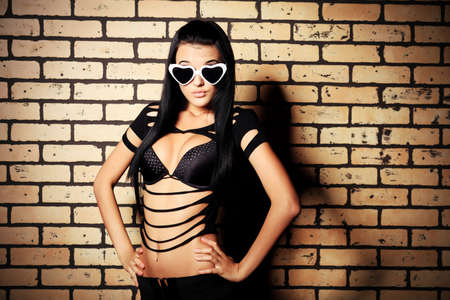 Fashion photo, a model is posing over brick wall. photo