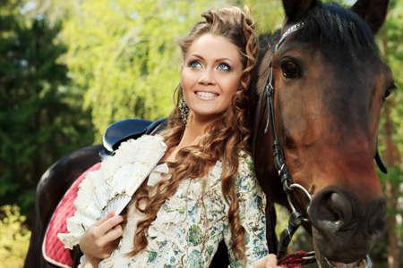 femme et cheval: Belle jeune femme en robe médiévale avec une piscine extérieure de cheval.
