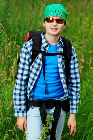 knapsack: A boy teenager with knapsack posing outdoor. Tourism, active life.