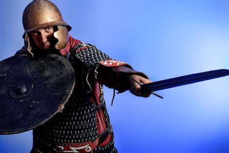 espadas medievales: Retrato de un caballero medieval masculino en armadura sobre fondo azul.