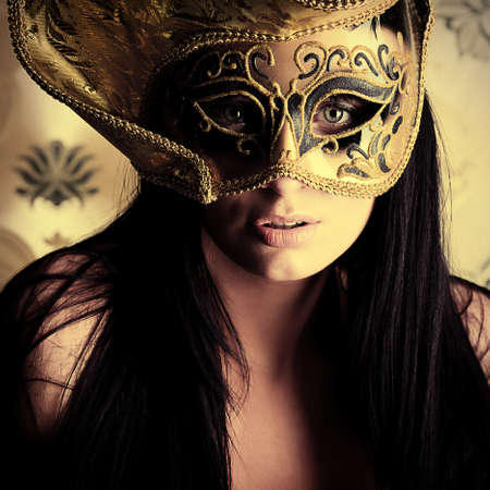nude woman posing: Shot of a sexy woman in a mask over vintage background.
