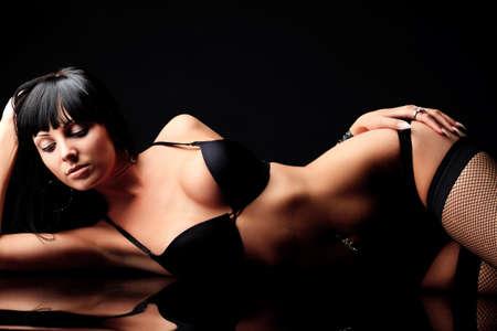 sexy fille nue: Tir d'une femme sexy en lingerie noire sur fond noir. Banque d'images