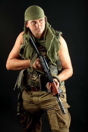 Shot of a conceptual soldier painted in khaki colors. Over black background. photo