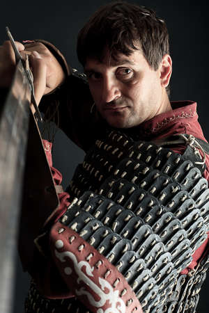 Portrait of a medieval male knight in armor over black background. photo