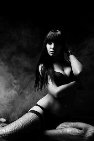young girl nude: Shot of a sexy woman in black lingerie over dark background with smoke.