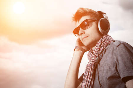 Portrait of a handsome young man in headphones posing\ outdoor.