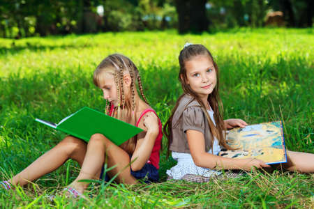 Two cheerful girls reading books outdoors. photo