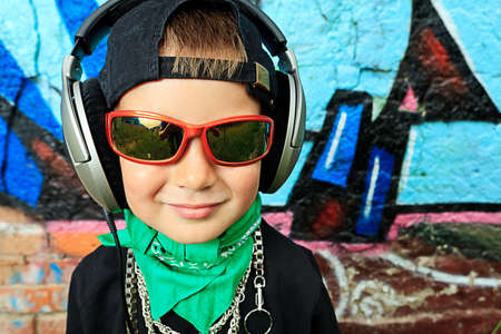 Portrait of a trendy little boy  with headphones outdoors. Stock Photo - 10489632