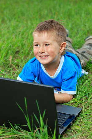 Portrait of a little boy lying with his laptop on a grass at a park. Stock Photo - 10489603