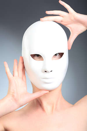 cosplay: Shot of a woman in white mask over grey background.