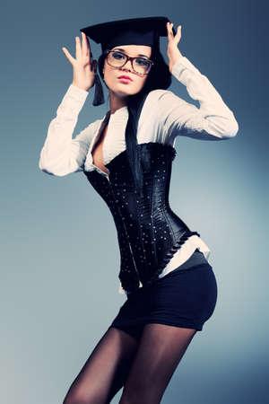 educacion sexual: Una atractiva mujer joven con gafas posando sobre fondo gris. Foto de archivo