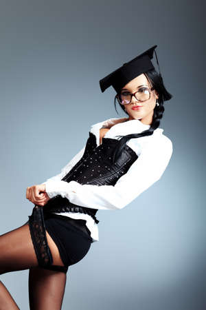 Sexy young woman in spectacles posing over grey background. photo