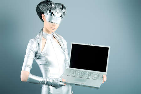 communication metaphor: Shot of a futuristic young woman with a laptop.  Stock Photo