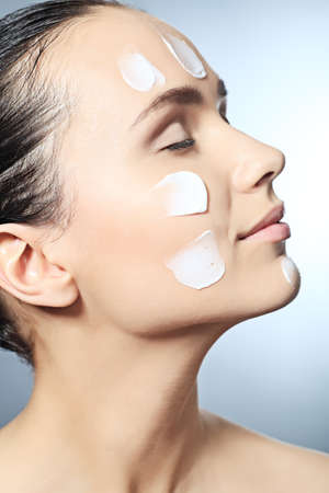 woman face close up: Portrait of beautiful spa girl with cream on her face. Stock Photo
